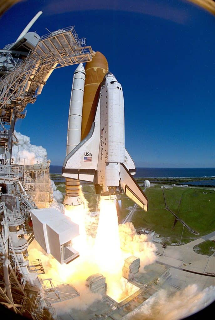 The space shuttle making its way into orbit from the earth